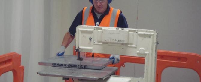 fieldmans-worker-using-machinery-to-cut-floor-panel